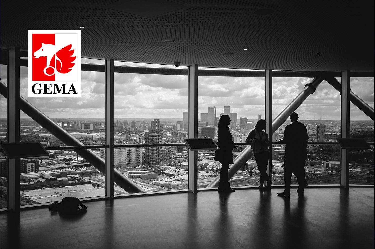 Contribution image in black and white with GEMA logo on it. Shows an empty office with people standing at a glass facade.