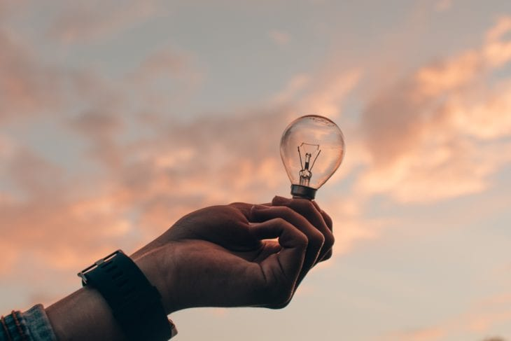 Person holds lightbulb in front of sky as a sign of creativity