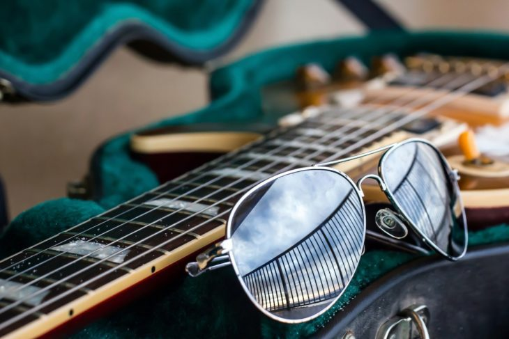 Guitar case with guitar and sunglasses symbolizes work-life balance for musicians